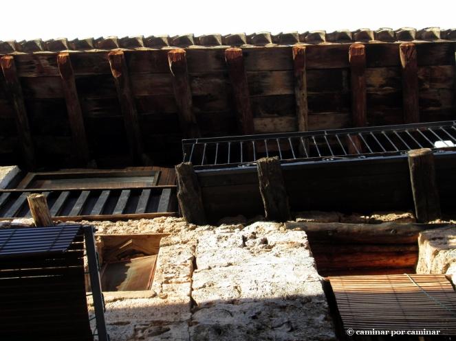 Alegoría a la madera: alero, vigas toscas de la balconada, barandilla, ventanas y persianas
