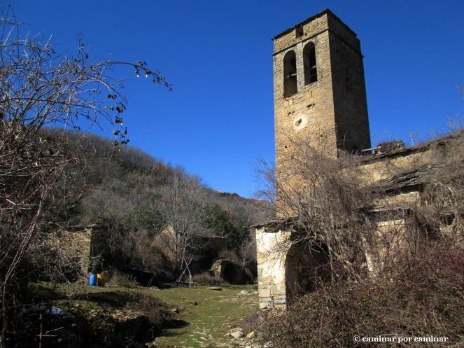 La esbelta torre de la iglesia no puede ocultar su primitiva función defensiva; el caxicar que calentó al pueblo al fondo
